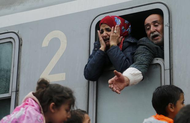 Migrants react after boarding a train at the station in Tovarnik, Croatia