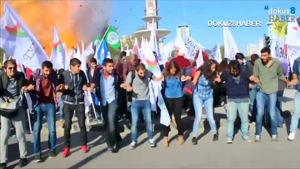 Protesters dance during a peace rally as a blast goes off in Ankara, Turkey, Oct. 10, 2015, in this still image taken from a video posted on a social media website.