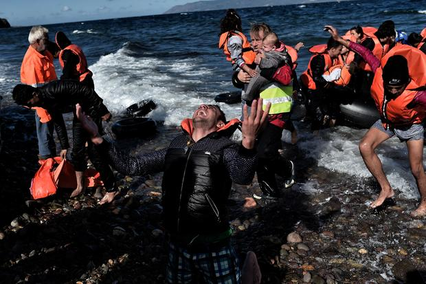 A man reacts as he arrives with other refugees and migrants on the Greek island of Lesbos