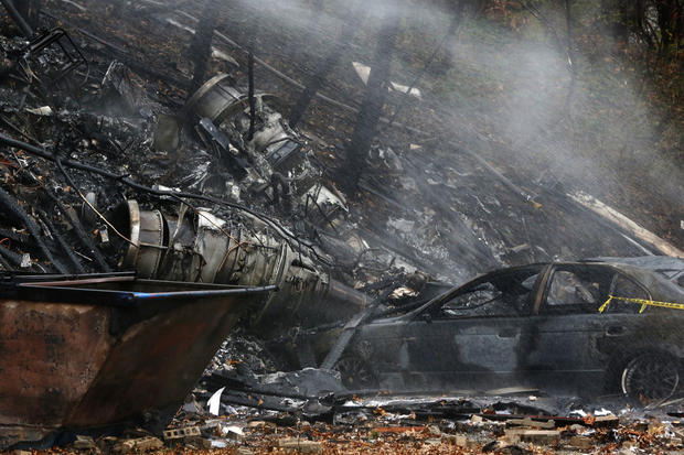 A charred car and aircraft debris smolder where authorities say a small business jet crashed into an apartment building in Akron, Ohio, Nov. 10, 2015.