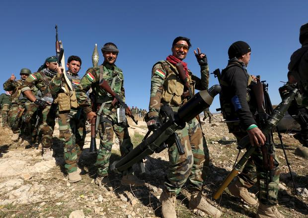 Members of the Kurdish peshmerga forces gather in the town of Sinjar, Iraq