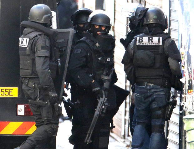 French special police forces arrive at the scene as shots are exchanged in Saint-Denis, France, near Paris, Nov. 18, 2015, during an operation to catch suspects in the deadly attacks in the French capital.