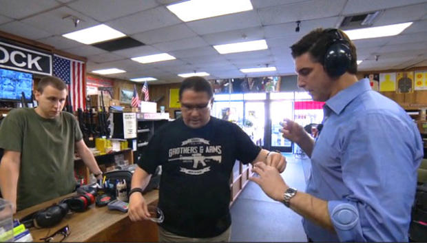CBS News correspondent Carter Evans at Riverside Magnum Gun Range with employees Mike McGee, left, and John Galletta, right