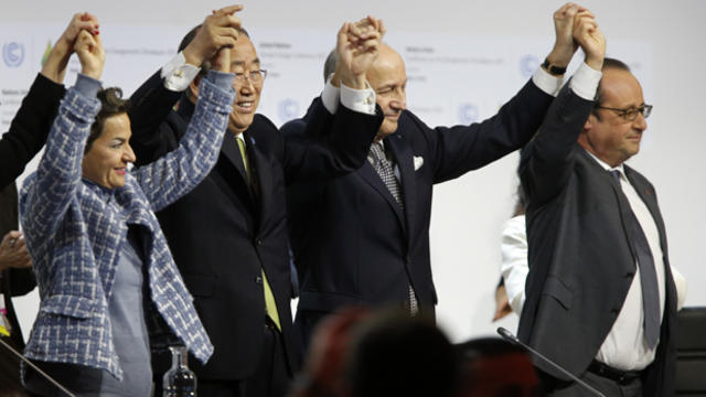 Laurent Fabius, center, French foreign affairs minister and president-designate of COP21, raises hands with U.N. Secretary-General Ban Ki-moon, second left, and France's President Francois Hollande, right, after the adoption of a historic global warming p