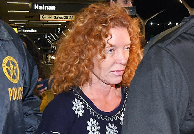 Tonya Couch is taken by authorities to a waiting car after arriving at Los Angeles International Airport Dec. 31, 2015, in Los Angeles.