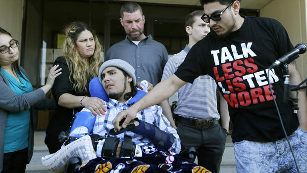 Alex Lemus, right, grasps his brother Sergio Molina's hand, front, as they gather with their mother Maria Lemus, center left, Tim McLaughlin, center, and his son Isaiah McLaughlin after a juvenile court hearing for Ethan Couch Feb. 19, 2016, in Fort Worth, Texas. Sergio Molina and Isaiah McLaughlin were injured in an accident caused by Couch.