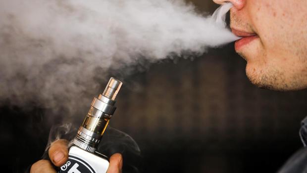 A man smokes an electronic cigarette vaporizer, also known as an e-cigarette, in Toronto Aug. 7, 2015.