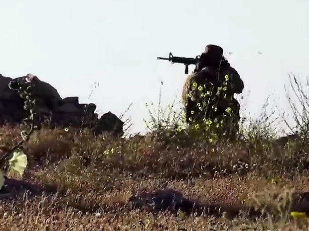 ​An image taken from video posted online by ISIS purportedly shows one of the group's militants firing on a Kurdish Peshermga position during an intense battle north of Mosul