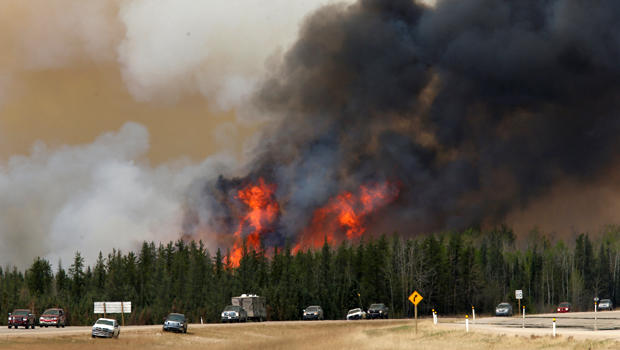 A wildfire burns as evacuees who were stranded north of Fort McMurray, Alberta, Canada, head south of the city on Highway 63, May 6, 2016.