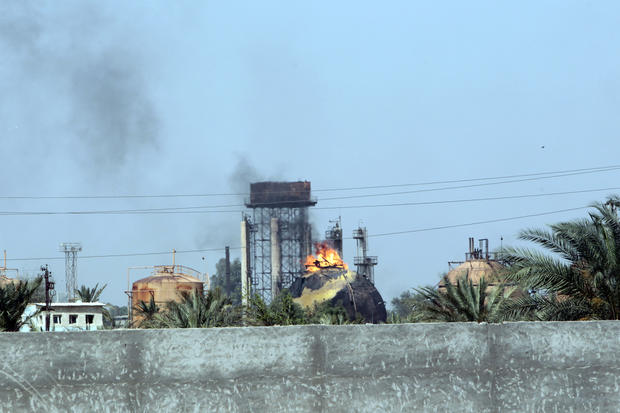 Flames and smoke rise from tanks after an ISIS suicide bomb attack on the Taji gas plant, about 12 miles north of the Iraqi capital Baghdad