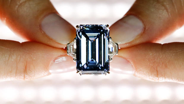 """A Christie's employee poses with the 14.62 carats """"Oppenheimer Blue"""" diamond during a preview in Geneva, Switzerland, on May 12, 2016."""