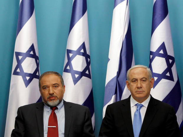 Israel's Prime Minister Benjamin Netanyahu (R) sits next to then-Foreign Minister Avigdor Lieberman