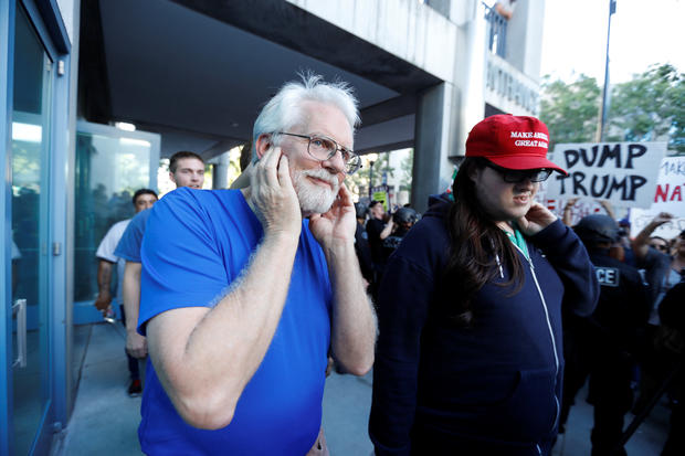 Donald Trump supporter covers his ears as he walks past demonstrator outside Trump rally in San Jose, California, on June 2, 2016