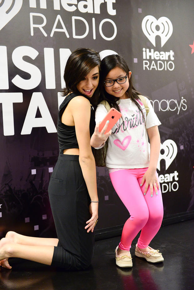 Singer Christina Grimmie poses with a fan at Macy's iHeartRadio rising star in-store performance on May 16, 2015, in Whitehall, Pennsylvania.