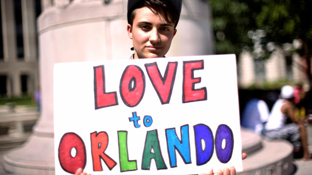 Ciaran Lithgow of Washington, D.C., holds a sign of condolence in Washington for victims of the attack on a gay nightclub in Orlando, Florida, on June 12, 2016.