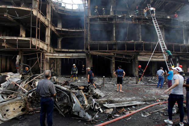 People gather at site of suicide car bombing in Karada shopping area in Baghdad on July 3, 2016
