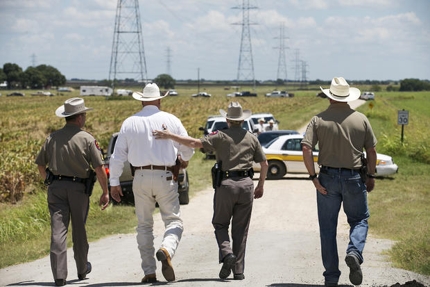 "​Texas Department of Public Safety Trooper Robbie Barrera, center right, puts her arm around Caldwell County Sheriff Daniel Law as he arrives on the scene of a hot air balloon crash July 30, 2016, near Lockhart, Texas, causing what authorities described as a ""significant loss of life."""