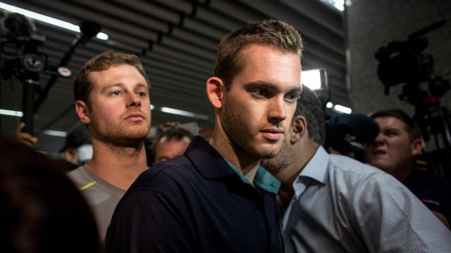 U.S. Olympic swimmers Gunnar Bentz, left, and Jack Conger leave police headquarters at the international departures terminal of Rio de Janiero's Galeo international airport on Aug. 18, 2016, in Rio de Janiero, Brazil.