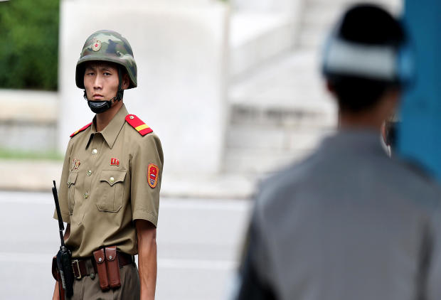 A North Korean soldier looks on as South Korean and United Nations officials visit after attending a ceremony to commemorate the 62nd Anniversary of the Korean War armistice agreement at Panmunjom on July 27, 2015, in South Korea.