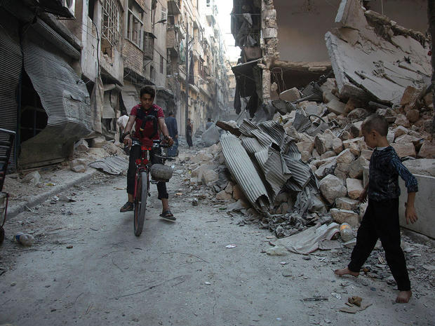 Syrian boys play amid rubble following an airstrike on Aleppo's rebel-controlled neighbourhood of Karm al-Jabal