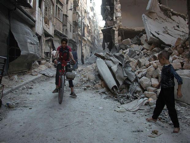 Syrian boys play amid rubble following an airstrike on Aleppo's rebel-controlled neighbourhood of Karm al-Jabal