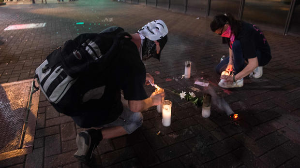 Protesters light candles on Sept. 22, 2016, at the site where Justin Carr was shot on Sept. 21, 2016, during a demonstration against police brutality in Charlotte, North Carolina, following the shooting of Keith Lamont Scott by police two days earlier and