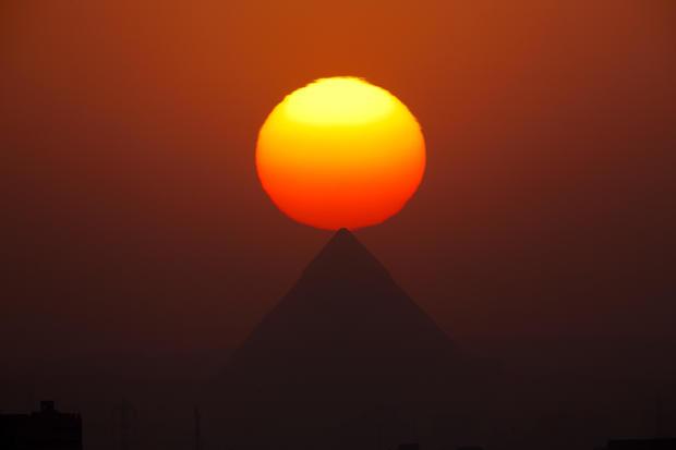 The sun sets over the Giza pyramids, near Cairo, Egypt, Aug. 19, 2016.