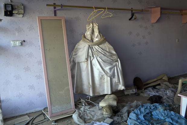 A wedding gown stands in a beauty parlor damaged in clashes between Iraqi security forces and Islamic State of Iraq and Syria fighters in Bartella, Iraq, Oct. 22, 2016.
