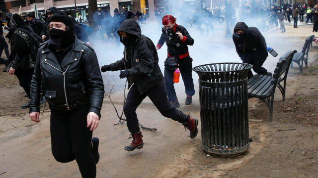 Activists race after being hit by a stun grenade while protesting against President Trump on the sidelines of the inauguration in Washington Jan. 20, 2017.