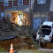 A pickup truck dangles over the edge of a sinkhole that swallowed parts of two residential yards Jan. 25, 2017, in the Philadelphia suburb of Glenside, Pa.