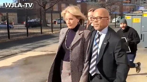 Education Secretary Betsy DeVos walks with a bodyguard to a SUV after protesters blocked her from entering Jefferson Middle School in Washington, D.C., on Feb. 10, 2017.