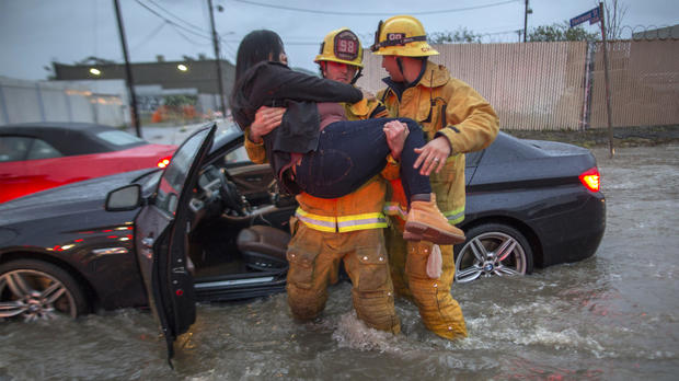 A firefighter carries a woman from her car after it was caught in street flooding as a powerful storm moves across Southern California on Feb. 17, 2017, in Sun Valley, California.