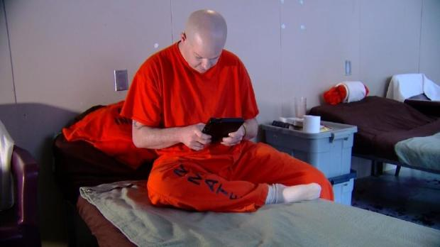 Dennis Nopper, an inmate in the Albany County Jail in New York, uses a tablet provided to inmates under a new program.