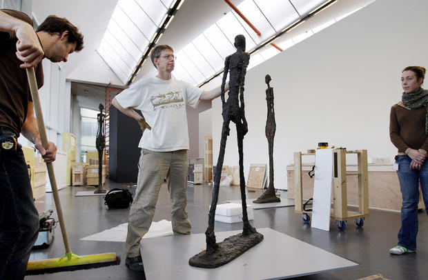 """Employees at the Kunsthal museum in Rotterdam, Netherlands, adjust the sculpture """"Walking Man"""" by Swiss artist Alberto Giacometti on Oct. 15, 2008."""