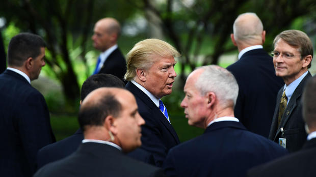 Then-Republican presidential nominee Donald Trump is surrounded by members of the Secret Service as he visits the tomb of former President Gerald Ford in Grand Rapids, Michigan, on Sept. 30, 2016.