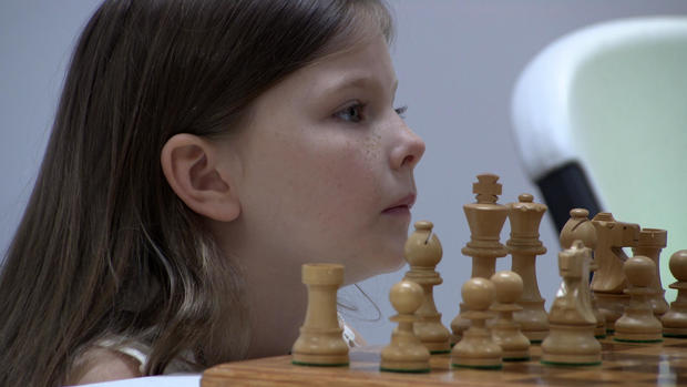 little-girls-face-next-to-chess-pieces.jpg