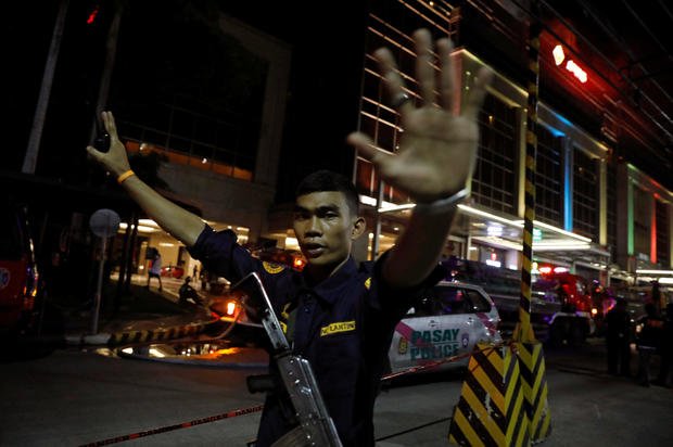 A security guard stops photographers from entering the vicinity of Resorts World Manila after gunshots and explosions were heard in Pasay City, Metro Manila, Philippines, June 2, 2017.