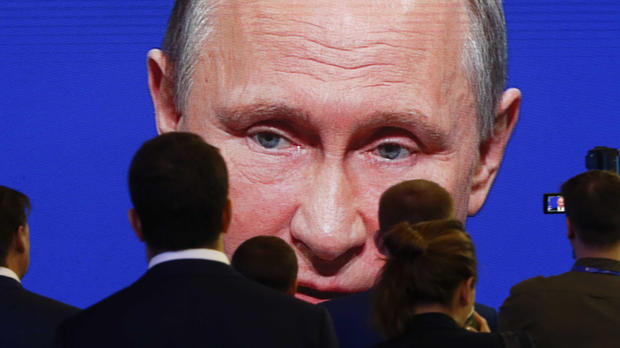 Participants of the St. Petersburg International Economic Forum gather near an electronic screen showing Russian President Vladimir Putin, who is speaking during a session of the forum in St. Petersburg, Russia, June 2, 2017.