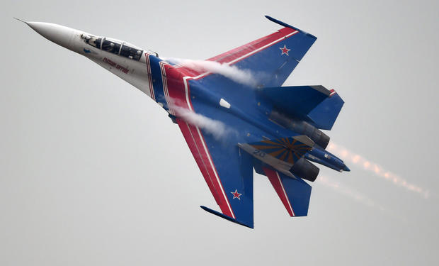 A member of the Russian air force's Knights aerobatic team performs in a SU-27 jet during a test flight ahead of an airshow in Zhuhai, China, on Nov. 10, 2014.