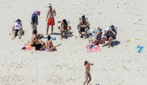 In this July 2, 2017, photo, New Jersey Gov. Chris Christie, right, uses the beach with his family and friends at the governor's summer house at Island Beach State Park in New Jersey.