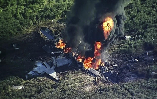 Smoke and flames rise from a military plane that crashed in a farm field in Itta Bena, Miss., July 10, 2017, in this frame from video.