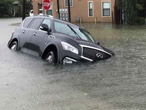 A vehicle sits half submerged in flood waters in a residential area in the aftermath of Hurricane Harvey in Houston