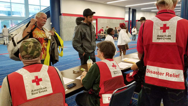 Evacuees arrive to seek shelter with Red Cross volunteers at the George Brown convention center after flood waters of Hurricane Harvey forced them to leave their homes in Houston
