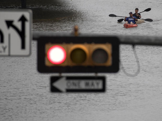 Men use kayaks to get through an intersection after heavy rain from Hurricane Harvey flooded Pearland, in the outskirts of Houston