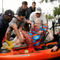 Sterling Broughton is moved from a rescue boat onto a kayak in Dickenson, Texas