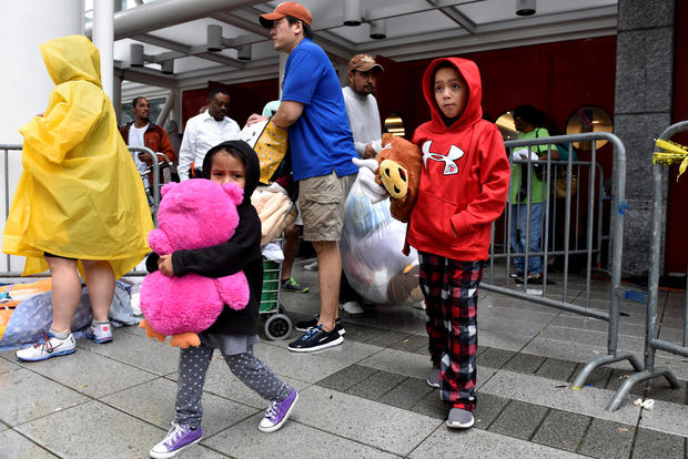 Evacuees carry their belongings outside of the George R. Brown Convention Center where over 9,000 people have taken refuge