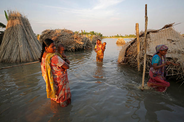 Women carry children as they make their way through a flooded area in Bogra