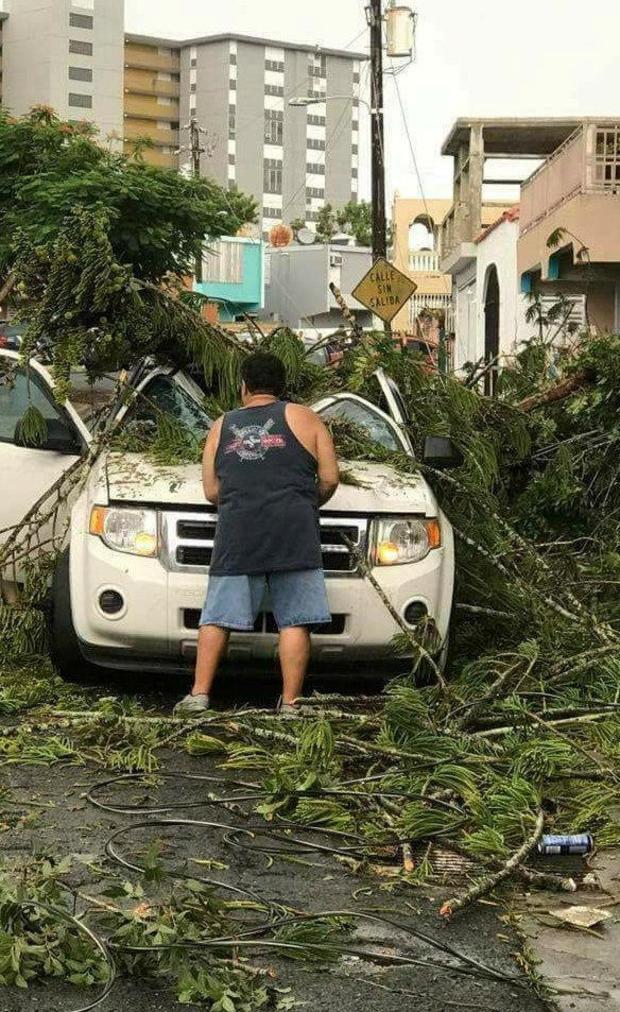 A man removes debris from a car following high winds as Hurricane Irma nears San Juan