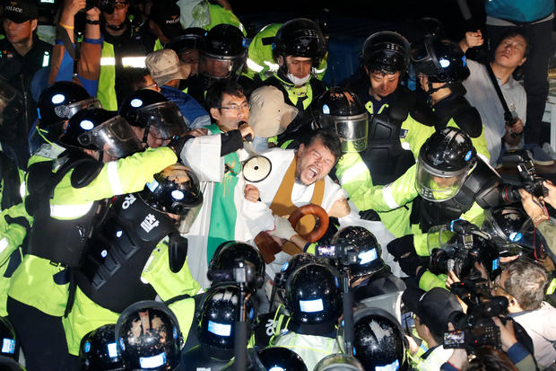 People scuffle with riot policemen during a protest opposing the deployment of a THAAD system in Seongju