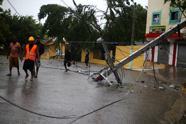 Locals walk past a fallen power pole as Hurricane Irma moves off the northern coast of the Dominican Republic, in Puerto Plata